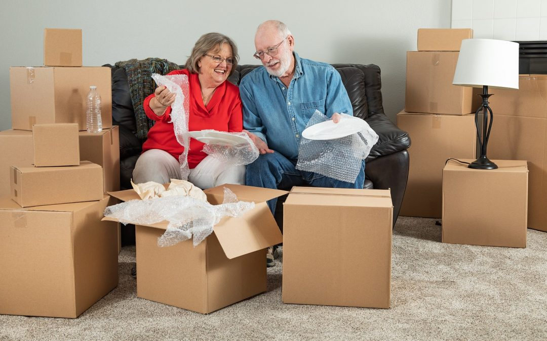 Senior couple downsizing and packing their belongings into boxes