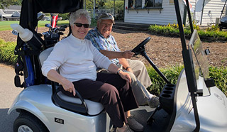 Two residents ride in a golf cart