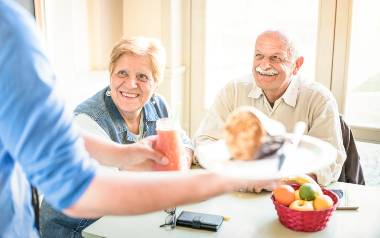 Two seniors being served a healthy meal